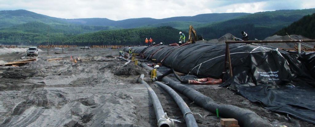 Mount St Helens Grade Building Structures Project, installing geotextile tubes in dry river bed