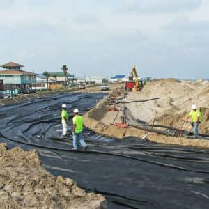 Installation of geotextile tubes on the beachfront in Grand Isle, LA, creating a dune to protect homes from storm surge and restore the beach after hurricanes
