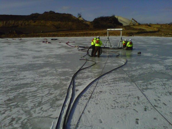 Staging the pump on the ice; silica sand mine operation in background