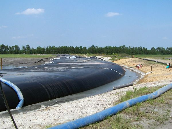 Geotextile tube filled to curve around perimeter of coal ash pond
