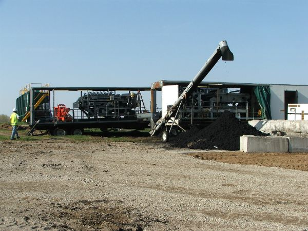 Belt filter press and stockpile of dewatered biosolids