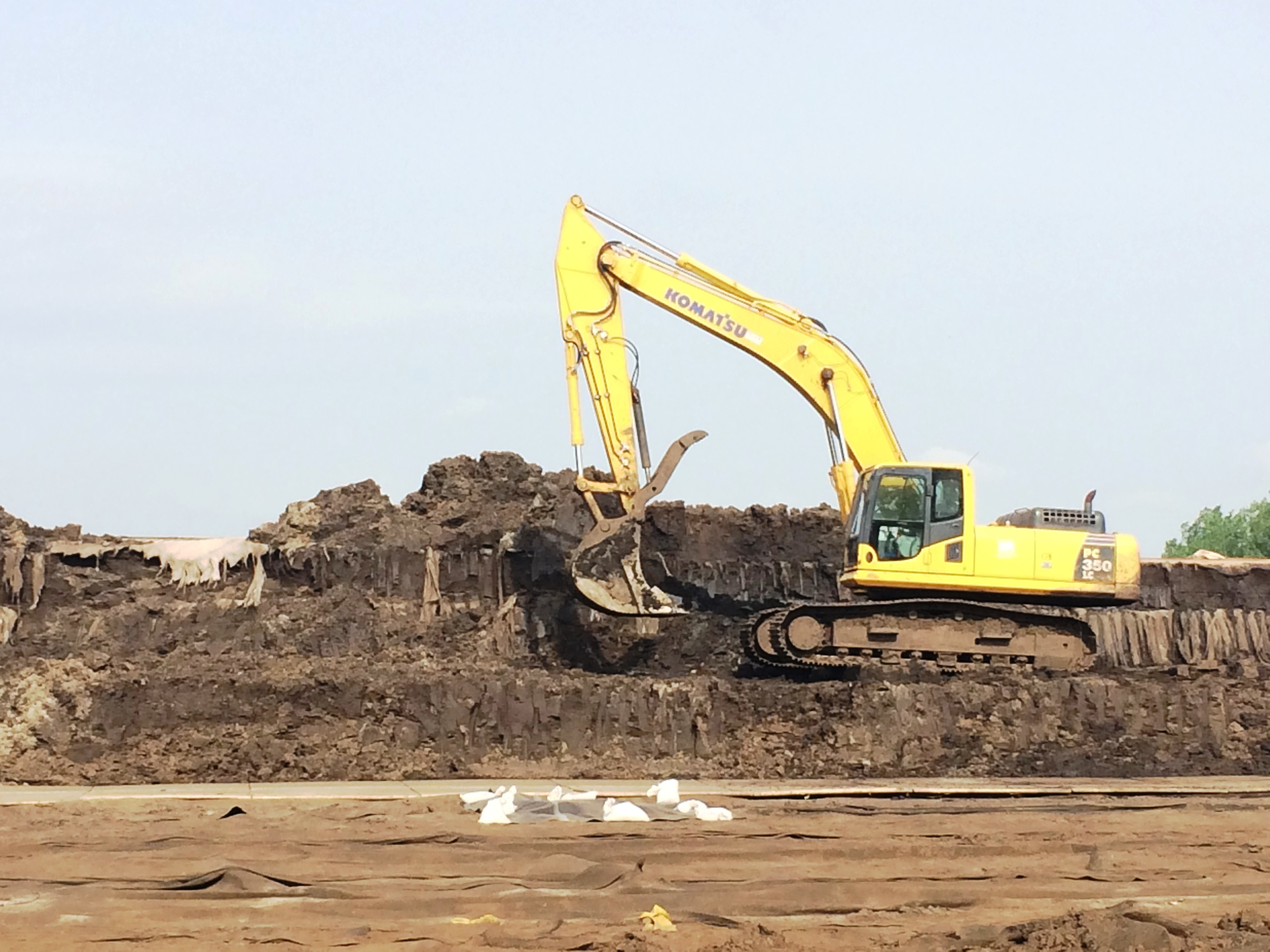 Excavator loads dewatered material into trucks