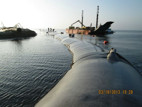 Filled geotextile tube curving around the end of the breakwater