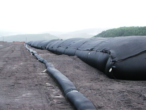 Looking down the side of a line of filled geotextile tubes