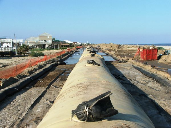Line of geotextile tubes stretching down the beach