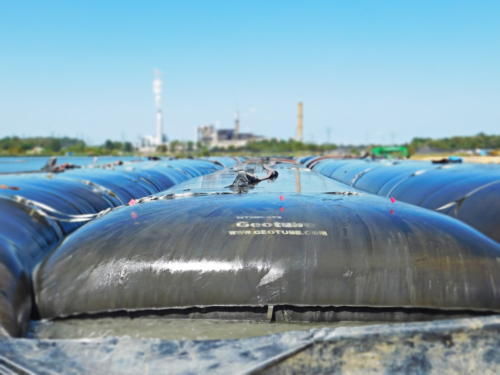 Geotextile tube, deployed, plumbed and partially filled with coal ash