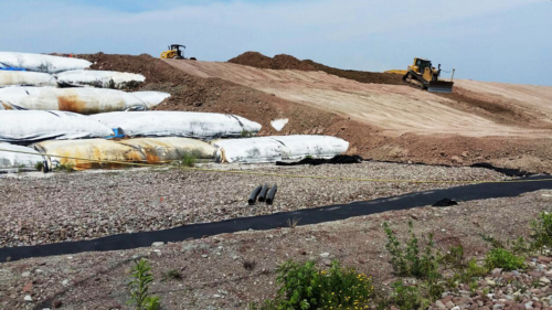 Dewatered geotextile tubes cap installation