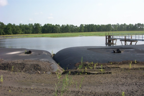 Active coal ash pond with geotextile tubes installed around perimeter