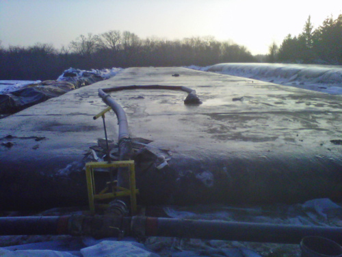 Geotextile tube dewatering the sand slurry, in snow and cold weather