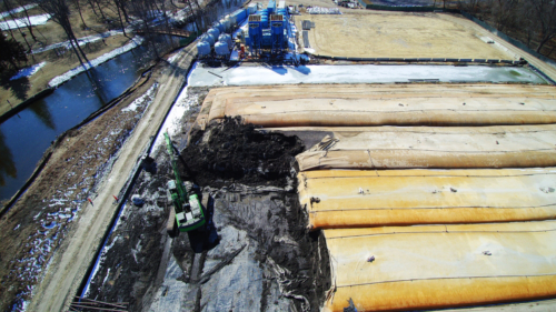 Dewatered geotextile tubes being removed from site